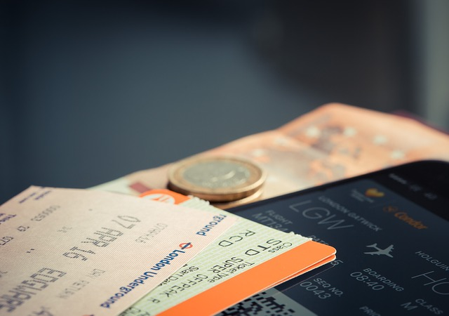 コインと電車の切符と航空機の旅程画面
